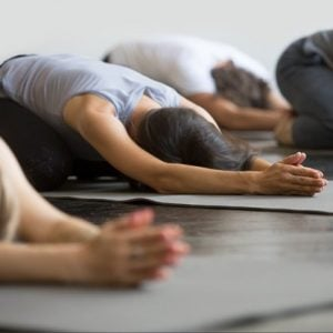 stock-photo-group-of-young-sporty-people-practicing-yoga-lesson-with-instructor-sitting-in-balasana-exercise-713186644