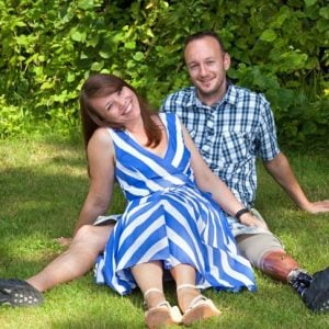stock-photo-happy-attractive-couple-relaxing-in-the-garden-sitting-close-together-on-the-grass-with-joyful-162286334