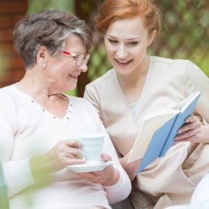 stock-photo-happy-grandma-in-glasses-holding-cup-of-coffee-and-watching-album-with-photos-with-her-nurse-698351416