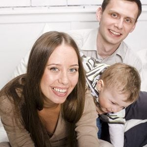 stock-photo-portrait-of-happy-family-mom-and-dad-playing-with-their-son-in-bed-76430527