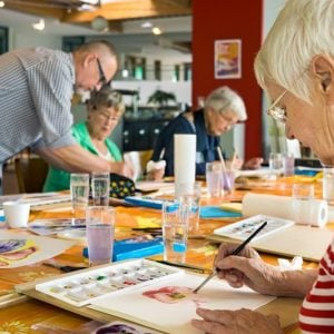 stock-photo-woman-in-striped-red-and-white-shirt-working-on-canvas-while-painting-with-brush-at-table-with-431933083